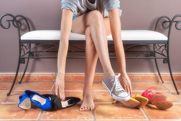 Mulher com pernas finas perfeitas, escolhendo tênis confortáveis ao invés de sapatos de salto alto desconfortáveis.