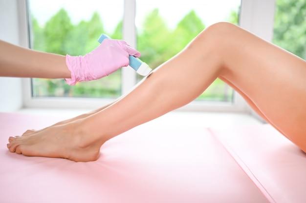 Mulher com pernas perfeitas muito bronzeadas e pele lisa com depilação de listras de cera