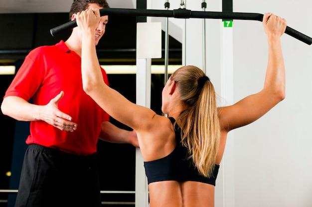 Mulher com personal trainer no ginásio