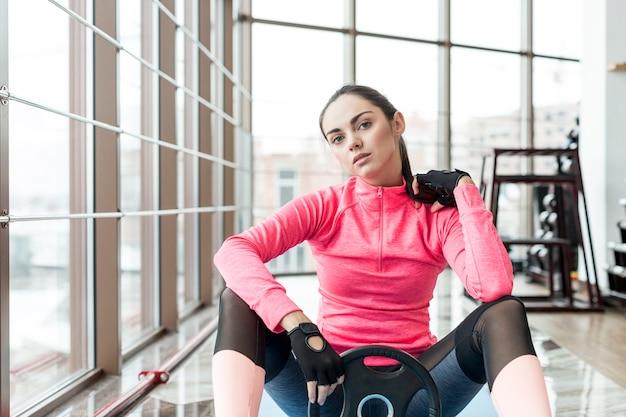 Mulher, com, peso, prato, sentando, em, ginásio