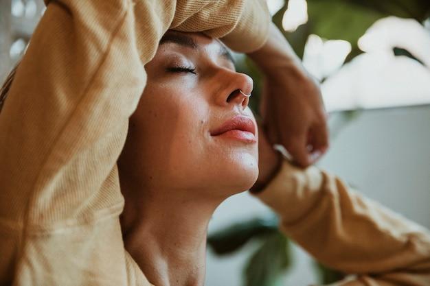 Mulher com piercing no nariz relaxando em casa
