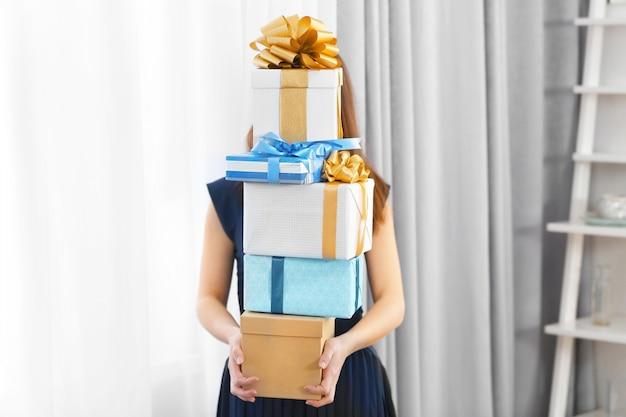 Mulher com pilha de presentes em casa