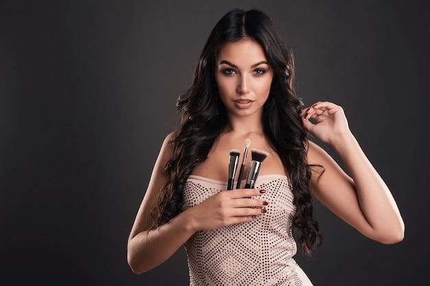 Mulher com pincéis de maquiagem