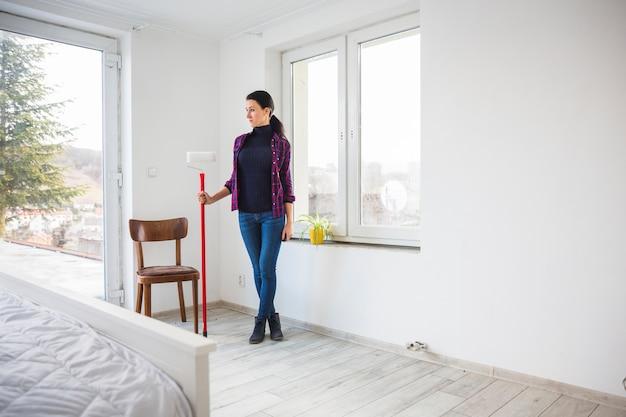 Mulher, com, pintar rolo, em, novo, apartamento