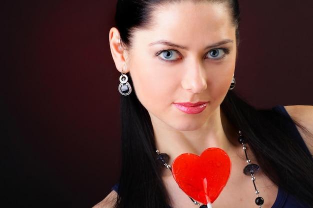 Mulher com pirulito vermelho em forma de coração