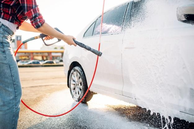 Mulher com pistola de água de alta pressão nas mãos lava a espuma do carro. mulher jovem na lavagem de automóveis self-service. limpeza de veículos externos em dia de verão