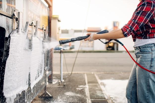 Mulher com pistola de água de alta pressão nas mãos limpa tapetes de carro, lava-jato sem contato. mulher jovem na lavagem de automóveis self-service. limpeza de veículos externos em dia de verão