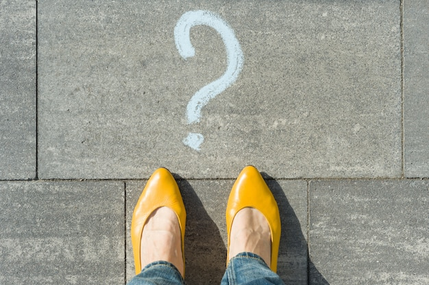 Mulher com ponto de interrogação na frente dos pés