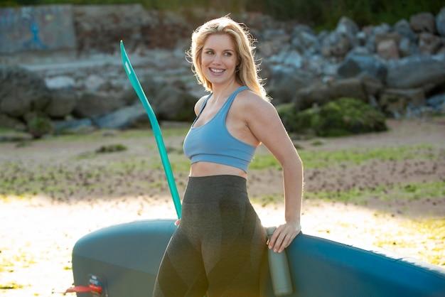 Mulher com prancha de paddleboard tiro médio