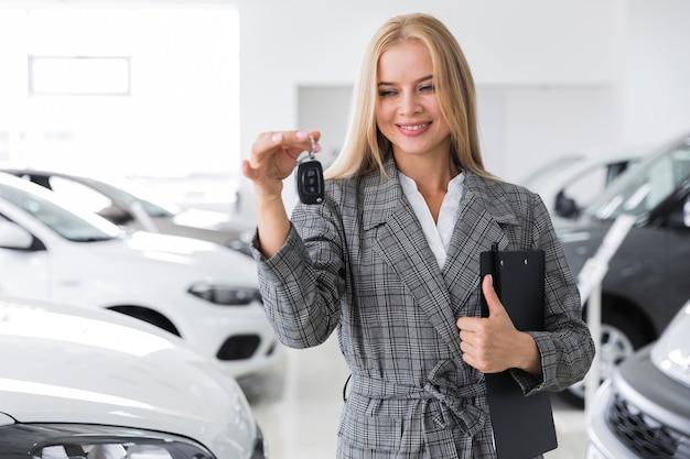 Mulher com prancheta preta segurando a chave do carro