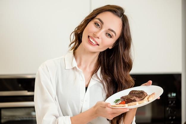 Mulher com prato de carne frita na cozinha em casa