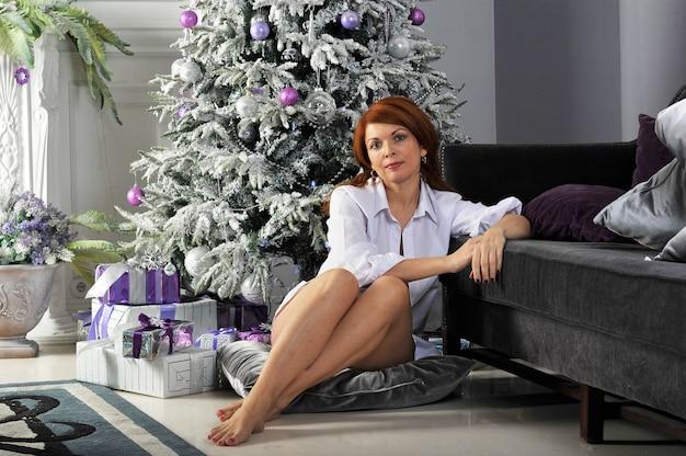 Mulher com presentes ao redor da árvore de natal
