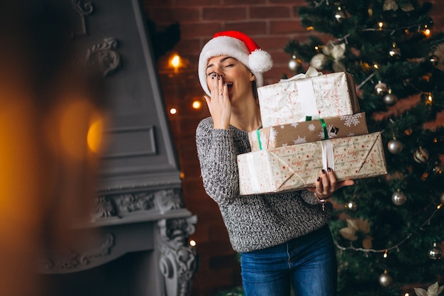 Mulher, com, presentes, ficar, frente, árvore natal