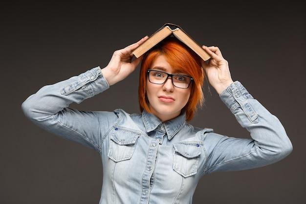 Mulher com problemas cansado de estudar, segure o livro na cabeça