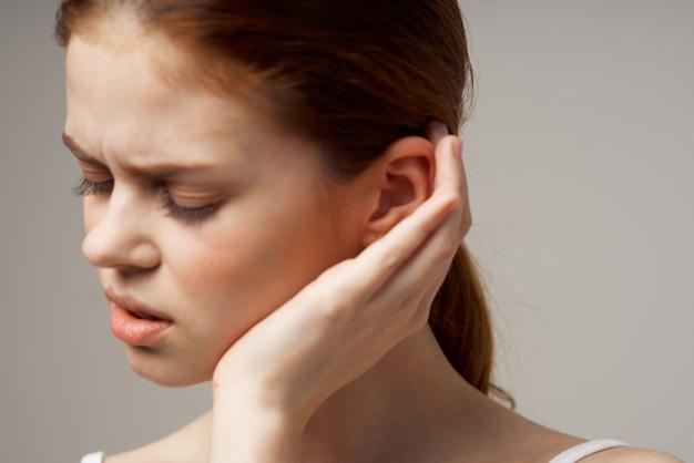 Mulher com problemas de audição em camiseta branca isolada em fundo