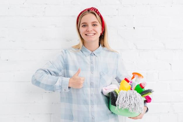Mulher com produtos de limpeza, mostrando sinal de ok