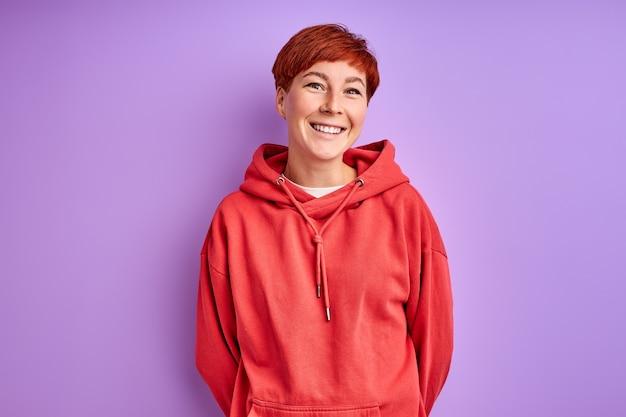 Mulher com pulôver vermelho sorrindo isolada na parede roxa, retrato