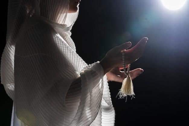 Mulher com pulseira sagrada rezando