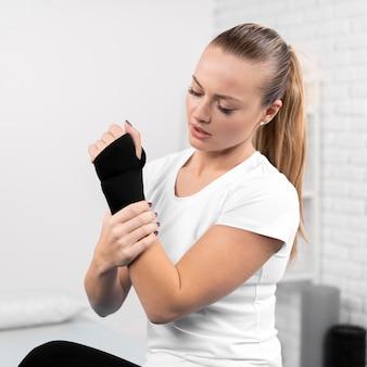 Mulher com pulso enrolado em fisioterapia