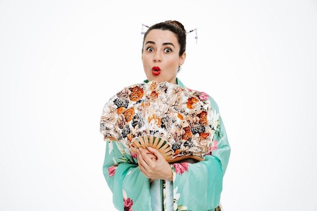 Mulher com quimono japonês tradicional segurando um leque e se surpreender com o branco