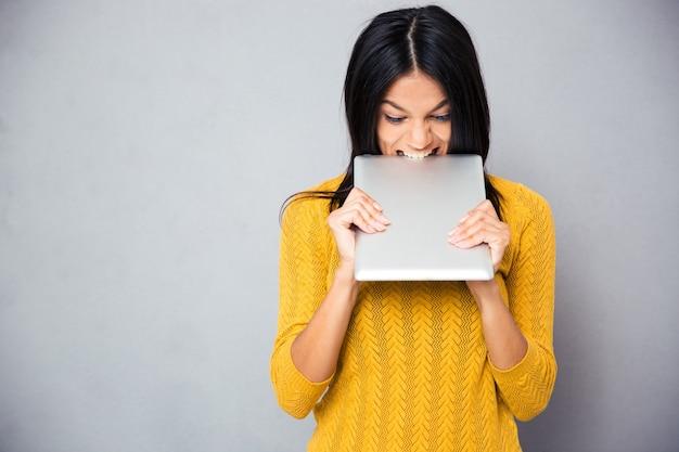 Mulher com raiva mordendo computador tablet