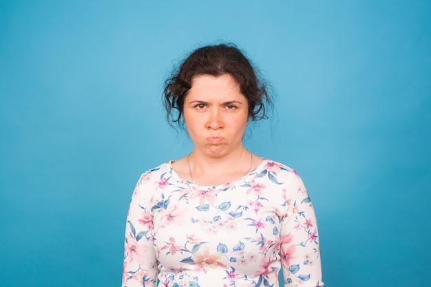 Mulher com raiva olhando para a câmera, lindo rosto feminino em fundo azul