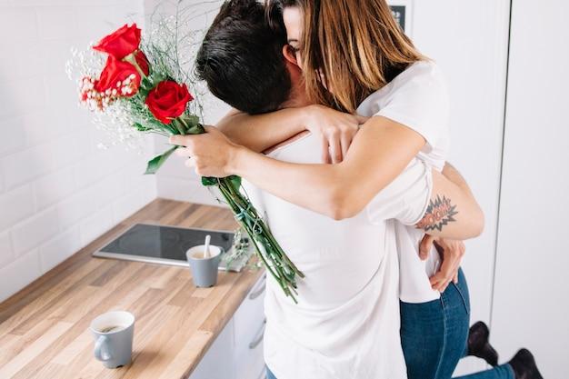 Mulher com ramo abraçando homem