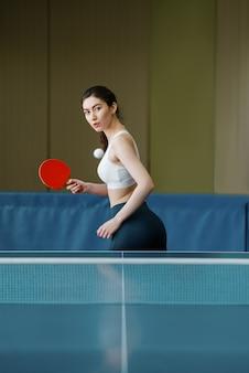Mulher com raquete e bola jogando pingue-pongue dentro de casa. mulher em roupas esportivas, treinando em clube de tênis de mesa