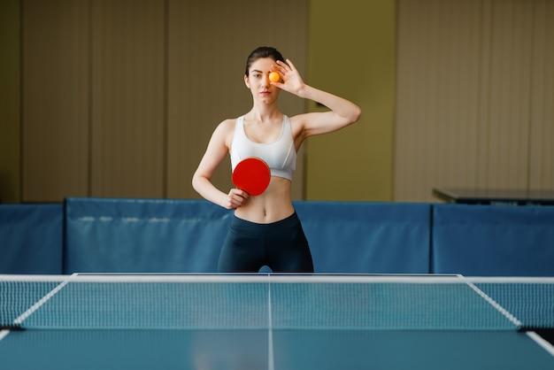 Mulher com raquete mostra bola de pingue-pongue dentro de casa.