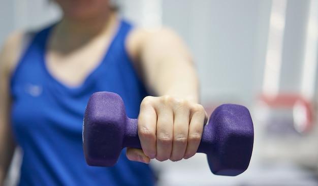 Mulher com relógio esportivo segurar levantando halteres com uma mão força lábio para treinamento de peso de músculo de bíceps de mama.