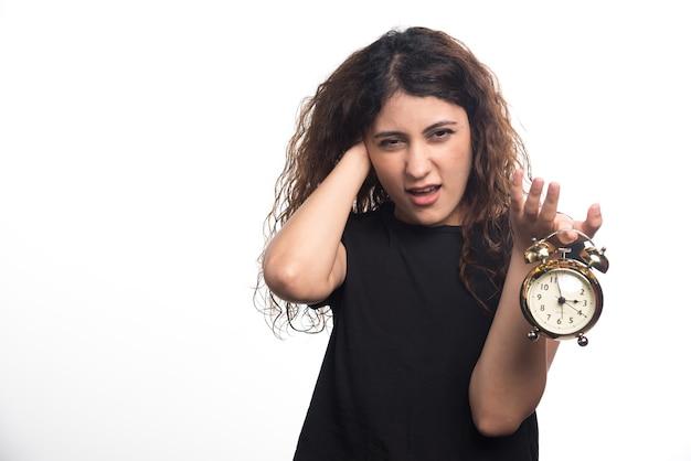 Mulher com relógio segurando sua cabeça no fundo branco. foto de alta qualidade