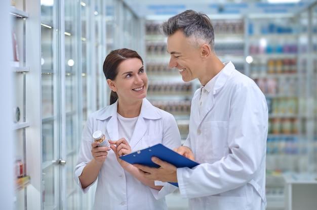 Mulher com remédio e homem com pasta na farmácia