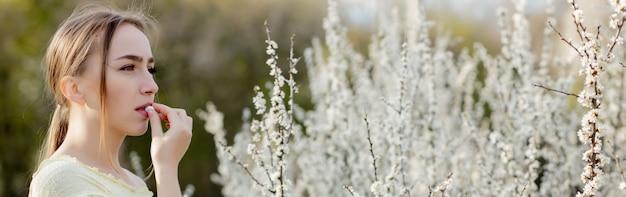 Mulher com remédio nas mãos fighting spring allergies outdoor - retrato de uma mulher alérgica, rodeada por flores sazonais