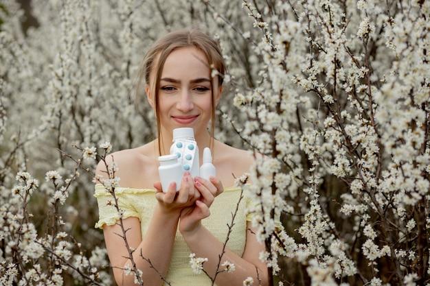 Mulher com remédio nas mãos, lutando contra as alergias da primavera ao ar livre