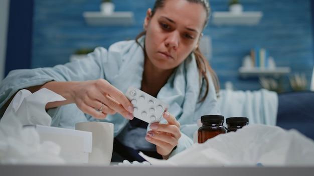 Mulher com resfriado olhando comprimidos com cápsulas e frascos com comprimidos