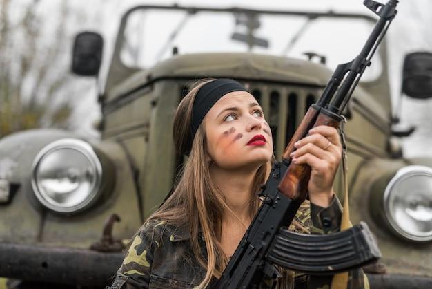 Mulher com rifle posando em carro militar