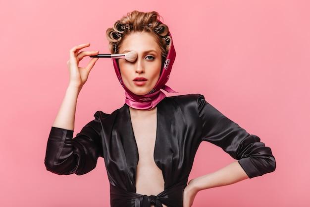Mulher com rolos de cabelo posa na parede rosa e cobre os olhos com pincel de maquiagem