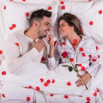 Mulher, com, rosa, tocar, nariz homem, cama
