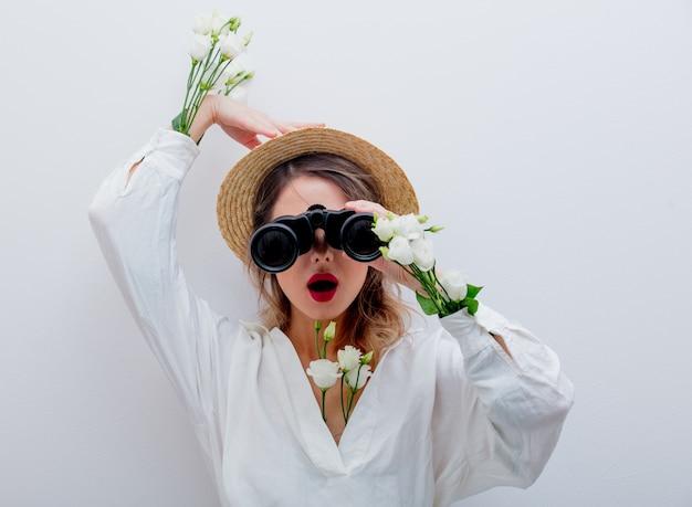 Mulher com rosas brancas em mangas com binóculo à procura de algo