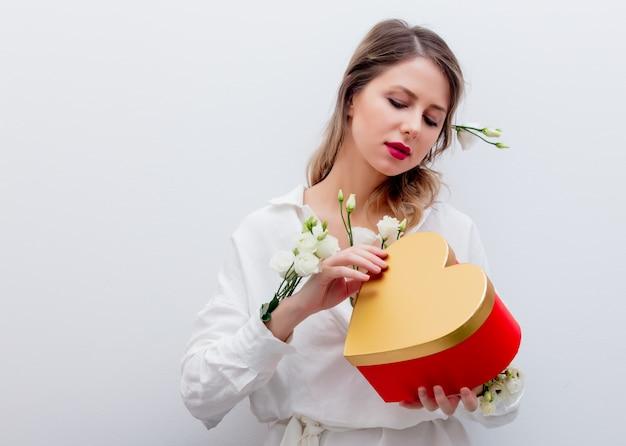 Mulher com rosas brancas, segurando uma caixa de presente de forma de coração.