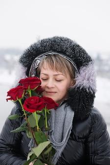 Mulher com rosas vermelhas ao ar livre no inverno