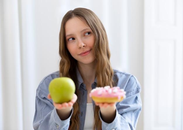 Mulher com rosquinha e maçã