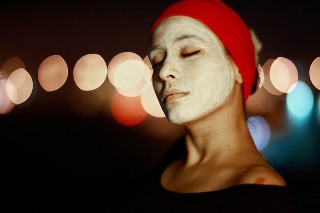 Mulher com rosto branco e fita vermelha