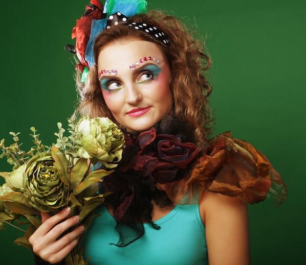 Mulher com rosto brigt segurando grandes flores verdes