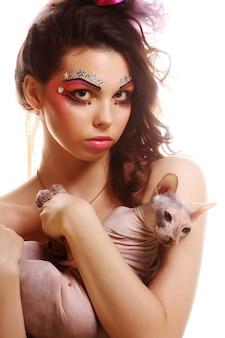Mulher com rosto criativo, segurando o gato sphynx