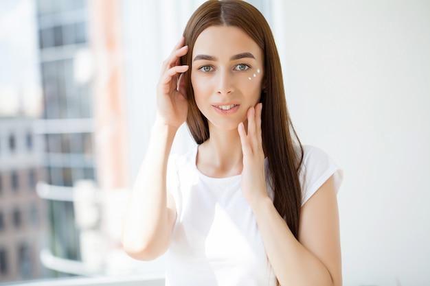 Mulher com rosto de beleza tocando retrato de pele facial saudável.