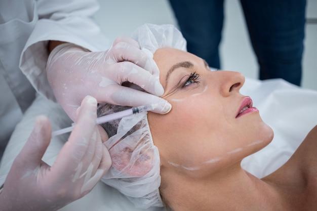 Mulher com rosto marcado, recebendo injeção de botox