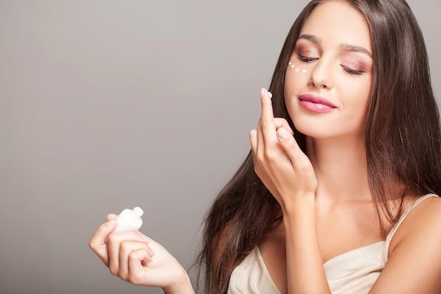 Mulher, com, rosto saudável, aplicando, creme cosmético, sob, a, olhos