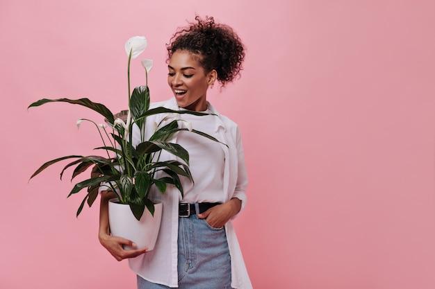 Mulher com roupa brilhante segurando uma planta na parede rosa