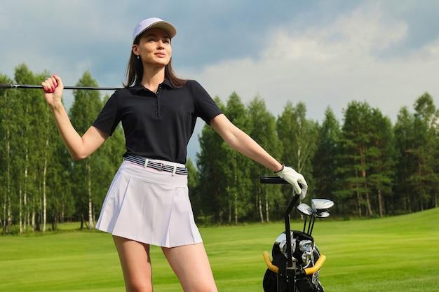 Mulher com roupa de golfe elegante de verão, caminhando com o saco de drivers no belo campo verde para o jogo de golfe.